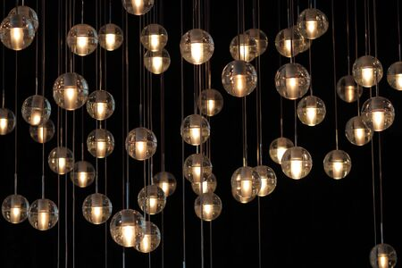 lighting balls on the chandelier in the lamplight, light bulbs hanging from the ceiling, lamps on the dark background, selective focus, horizontal Imagens