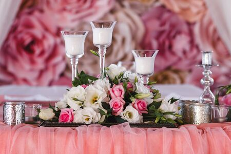 wedding table decorated with fresh flowers, candles and silver cups. Paper flowers in the background