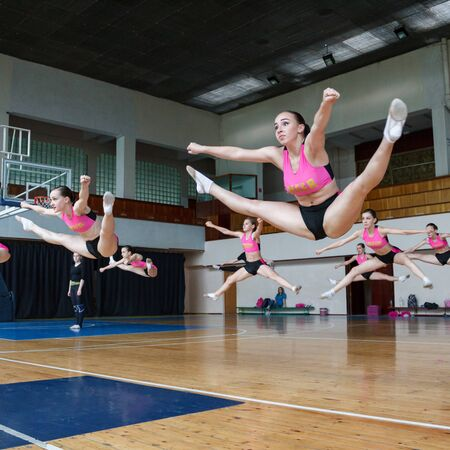 group of cheerleaders jumping in the air demonstrate perfect stretching, active pretty girls in action, horizontal twine, hands raised up, girls in black and pink suit on the background of the gym