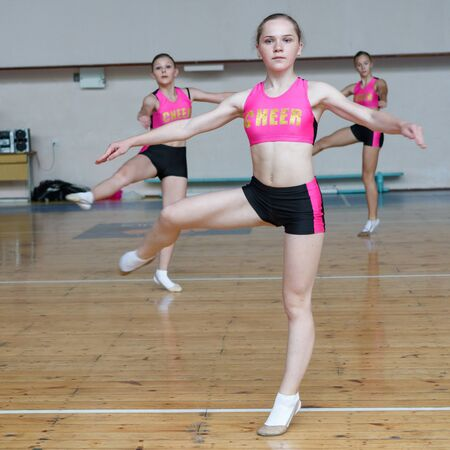Dancers shows off their moves - pirouette, girls in black and pink sportswear train at the gym, sport young woman rotates on one leg, cheerleader dancer doing pirouette Imagens