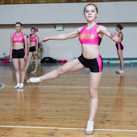 Dancers shows off their moves - pirouette, girls in black and pink sportswear train at the gym, sport young woman rotates on one leg, cheerleader dancer doing pirouette Фото со стока