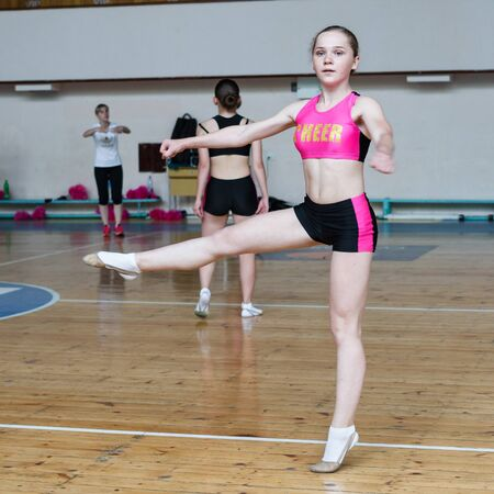 cheerleader dancer doing pirouette, dancers shows off their moves - pirouette, sport young woman rotates on one leg, girls in black and pink sportswear train at the gym