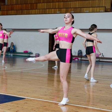 cheerleader dancer doing pirouette, dancers shows off their moves - pirouette, sport young woman rotates on one leg, girls in black and pink sportswear train at the gym Фото со стока