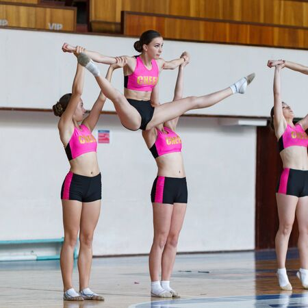young cheerleaders working out in sports club, group of cheerleaders with pom-poms in their hands, girls with pompons on the background of the gym, girl in action jumping in the air, horizontal twine
