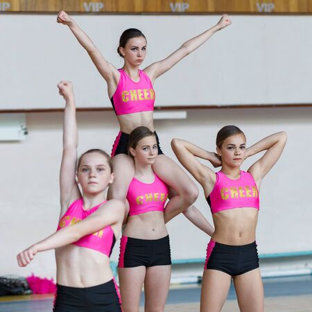 attractive young cheerleader girl sits on the shoulders of a teammate, beautiful girls in black and pink sportswear sitting on the neck, cheerleader group perform trick