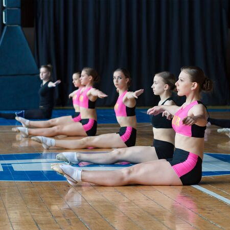 athlete warming up before training, cheerleaders in black and pink sportswear doing some stretching exercises, young woman sitting on the floor and spreading his hands to the sides