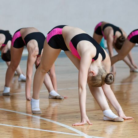 group of cheerleaders train at the gym, sport girls with perfect body working out in sports club, young woman in black and pink sportswear doing some stretching exercises and warming up at the gym