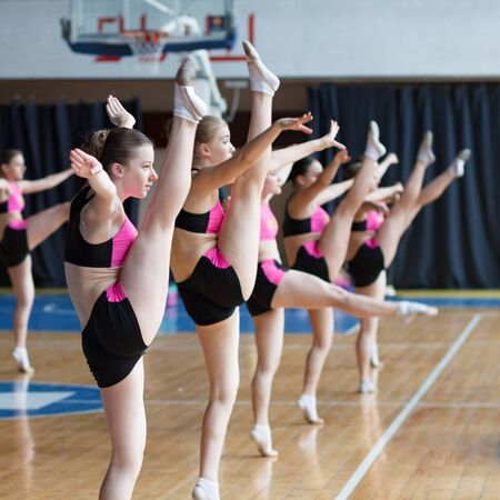 young cheerleaders working out in sports club, dancers practicing mixed dance and stretching, extending leg up, girls doing acrobatic and flexible tricks, stretching workout, vertical twine Фото со стока