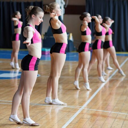 cheerleaders train at the gym, smiling beautiful girl in black and pink sportswear showing strength and power, sport young women with perfect body working out in sports club Imagens