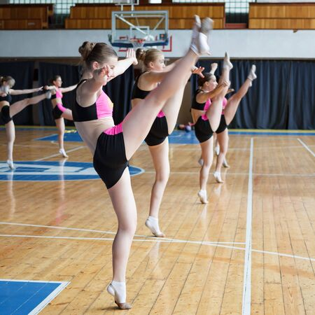 young cheerleaders working out in sports club, dancers practicing mixed dance and stretching, extending leg up, girls doing acrobatic and flexible tricks, stretching workout, vertical twine Imagens - 139676660