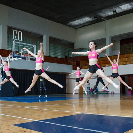 active pretty girls in action, group of cheerleaders jumping in the air demonstrate perfect stretching, hands raised up, girls in black and pink suit on the background of the gym, horizontal twine Фото со стока
