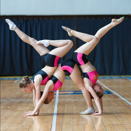 girls stand on hands and doing acrobatic and flexible tricks, girls standing upside down on her head, Handstand, cheerleaders working out in sports club, dancers practicing mixed dance and stretching