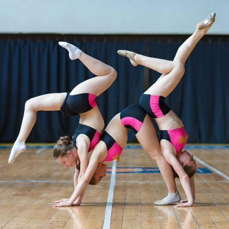 girls stand on hands and doing acrobatic and flexible tricks, girls standing upside down on her head, Handstand, cheerleaders working out in sports club, dancers practicing mixed dance and stretching Imagens - 139406108