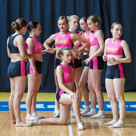 group of cheerleaders getting ready to do the trick, cheerleading group is preparing to perform stunt, attractive young dancers in black and pink suit on the background of the gym Imagens