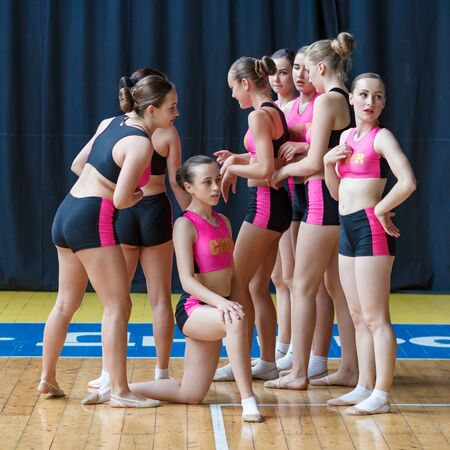 attractive young dancers in black and pink suit on the background of the gym, group of cheerleaders getting ready to do the trick, cheerleading group is preparing to perform stunt Imagens