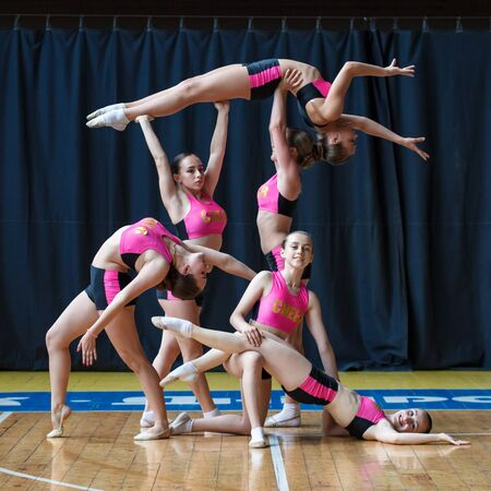 cheerleader group perform trick, smiling beautiful girls in black and pink sportswear shows off their moves, dancers hold the girl in their arms