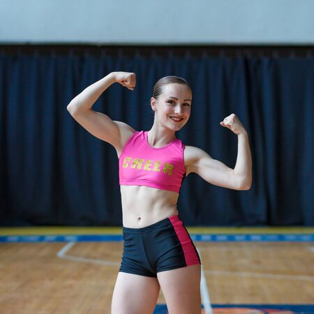 Smiling girls in black and pink sportswear flexing biceps, showing strength and power and looking at camera, sport woman with perfect body showing biceps, girl with fit body demonstrating muscles