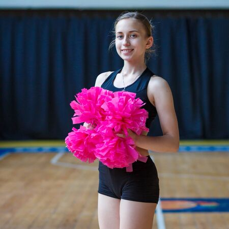girls in black sportswear with pink pompoms on gym, attractive young cheerleader working out in sports club, cheerleader with pom-poms in their hands smiling and posing at camera, full length Imagens - 140869464