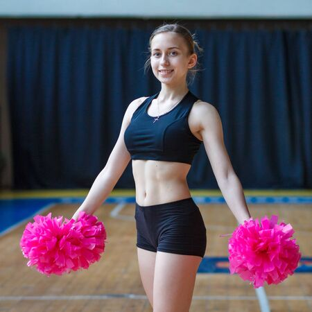 girls in black sportswear with pink pompoms on gym, attractive young cheerleader working out in sports club, cheerleader with pom-poms in their hands smiling and posing at camera, full length