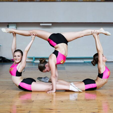 cheerleaders working out in the gym, girls standing upside down, handstand, girl stand on hands and doing acrobatic and flexible tricks, dancers practicing mixed dance and stretching, horizontal twine