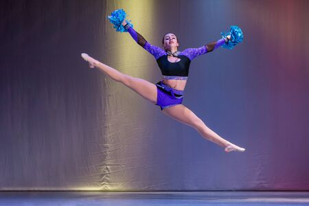athletes perform on stage, young cheerleaders perform at the cheerleading championship, girls in a jump, girls are holding pompons, hands raised up, toe touch, girl doing acrobatic and flexible tricks