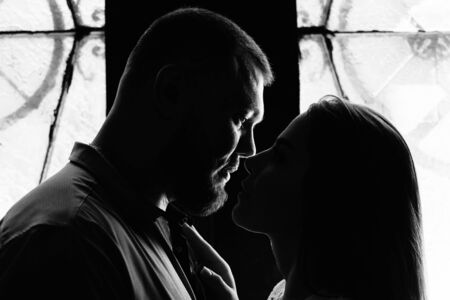 portrait of a romantic couple in a backlight from a window or door, silhouette of a couple in a doorway with a backlight, couple of lovers groom and bride at the window, girl holding flowers in hands Фото со стока
