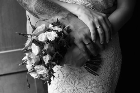 hands of the bride and groom with wedding rings, bride holds a wedding bouquet in hands, the groom hugs her from behind Фото со стока