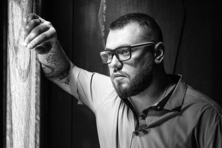 brutal bearded man with a tattoo on his arm, portrait of a man in dramatic light against a brown wooden wall, bearded male with tattoo dressed in a shirt, man wearing glasses looks in the side Фото со стока