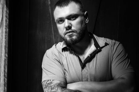 brutal bearded man with a tattoo on his arm, a portrait of a man in dramatic light against a brown wooden wall, attractive bearded male with tattoo on arm dressed in a shirt, man looks in the side