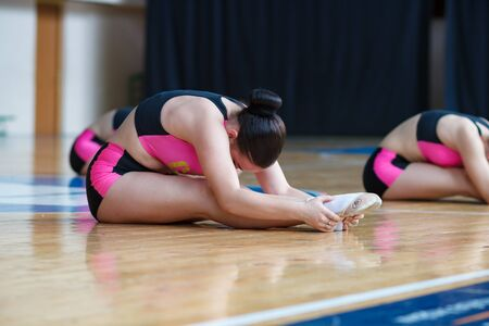 cheerleaders doing some stretching exercises, athlete warming up before training sitting on the floor, girl holds on outstretched legs and leans forward thus stretching the muscles Imagens