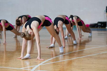 young woman in black and pink sportswear doing some stretching exercises and warming up at the gym, group of cheerleaders train at the gym, sport girls with perfect body working out in sports club