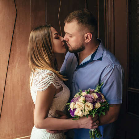portrait of a romantic couple, man and woman kissing in a dramatic light, girl holding flowers in hands, young beautiful bride in white dress holding wedding bouquet Imagens
