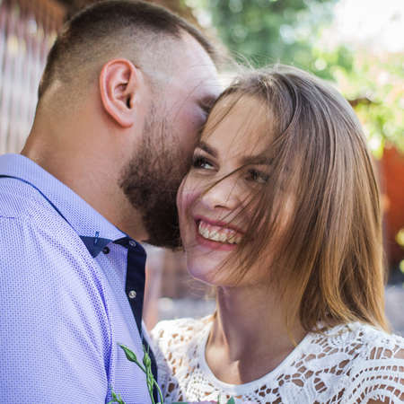 Young man whispering to woman or girlfriend, boyfriend telling surprising secret to his girl, man says nice words to his girlfriend, girl is smiling or laughing