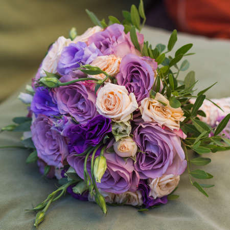 wedding bouquet on a green cushion, bouquet of bride from rose cream spray, rose bush, rose purple Memory Lane, violet eustoma, eucalyptus