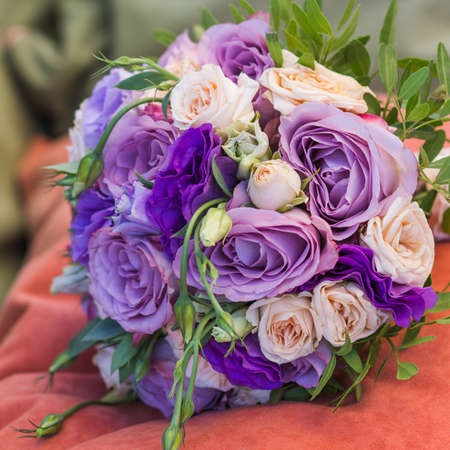 wedding bouquet on an orange pillow, bouquet of bride from rose cream spray, rose bush, rose purple Memory Lane, violet eustoma, eucalyptus