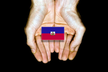 relief: Flag of Haiti in hands isolated on black background. Stock Photo
