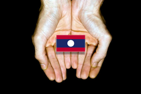 laos: Flag of Laos in hands isolated on black background.