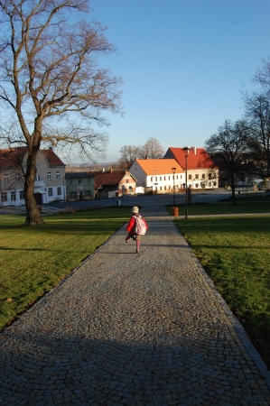 Schoolgirl goes through small town square with tall tree casting a long shadow photo
