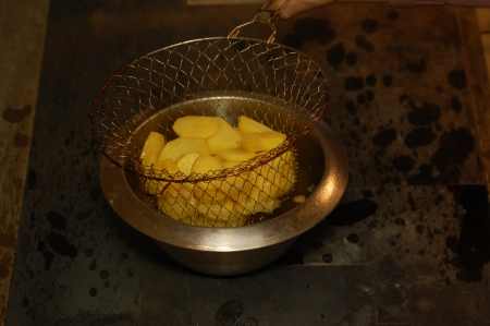 strainer: Strainer with potato slices in hot oil