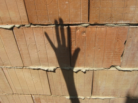 Shadow hand makes signs on unplastered porous brick wall Stock Photo - 25026412
