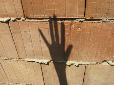 Shadow hand makes signs on unplastered porous brick wall Stock Photo - 25026410
