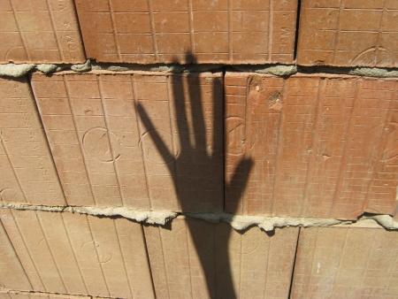 astral body: Sombra mano hace se�ales en la pared de ladrillo sin revocar porosa Foto de archivo