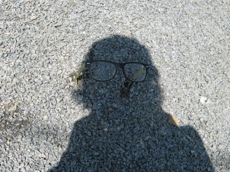 astral body: figura de la sombra en la grava con gafas Foto de archivo