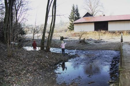 Two children throwing stones into the creek photo