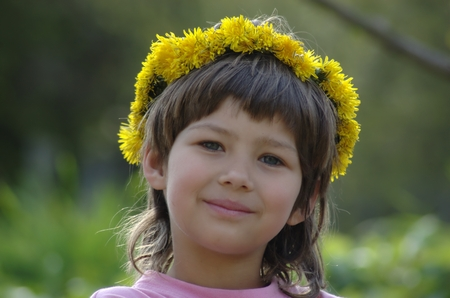 self indulgence: head of smiling girl with dandelion wreath on head