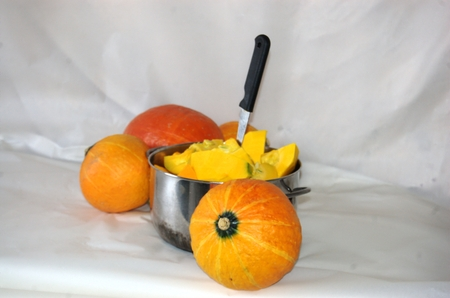 Pumpkin cut into small pieces, shiny pot and knife photo