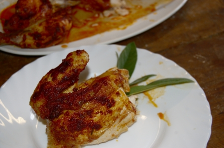 offshoot: Quarter of roast chicken with red pepper crust and a sprig of sage on a white porcelain plate.