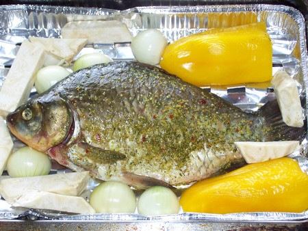 Crucian carp prepared for cooking on baking tray with yellow pepper, onion, celery