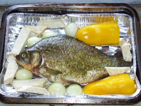 Crucian carp big fish prepared for cooking on metal hotplate with yellow pepper, onion, celery