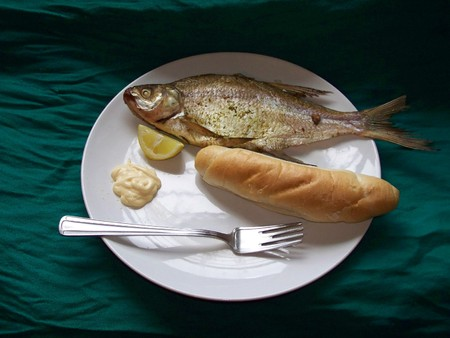 Bream - fish with lemon, mayonnaise and roll, baked, prepared on white ceramic plate on green textile background